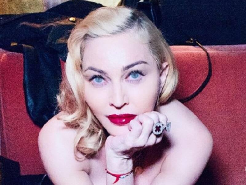 Apoiada em muleta, Madonna posa de topless em foto