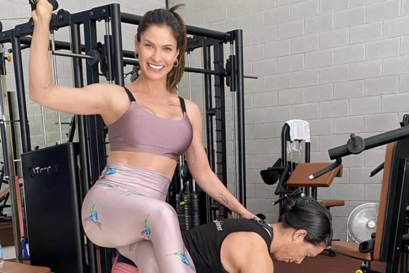 Andressa Suita aparece na academia sentada nas costas de sua personal